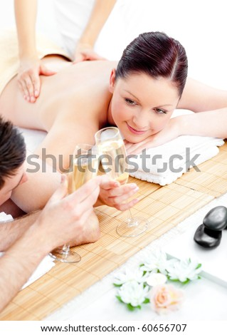 Caucasian young couple enjoying a back massage and drinking champagne in a spa center - stock photo