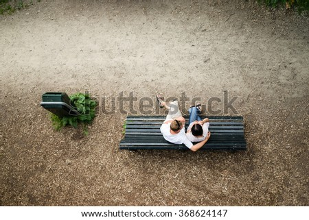 Caucasian young couple sitting on a park bench man protecting his girlfriend with love - stock photo