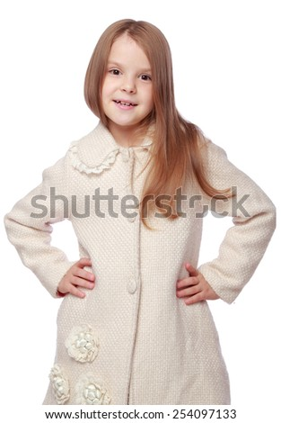 Caucasian young girl with healthy skin and well-groomed hair in a white coat - stock photo