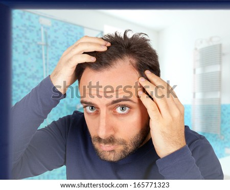 Caucasian young man controls hair loss in the bathroom - stock photo