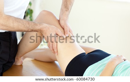 Caucasian young physical therapist giving a leg massage in a health center - stock photo