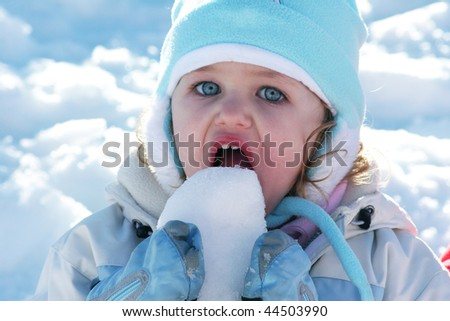 caucasian young toddler with blue eyes eating snow - stock photo