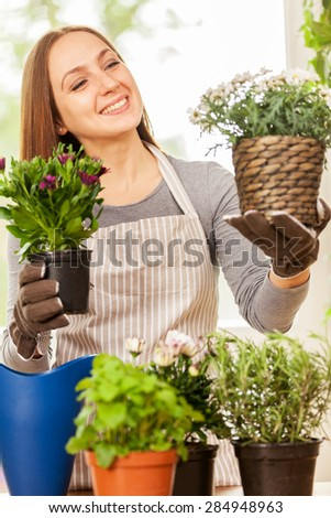 Caucasian young woman doing some gardening at home with her colorful plants - stock photo