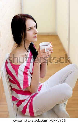 Caucasian young woman with cup of tea - stock photo