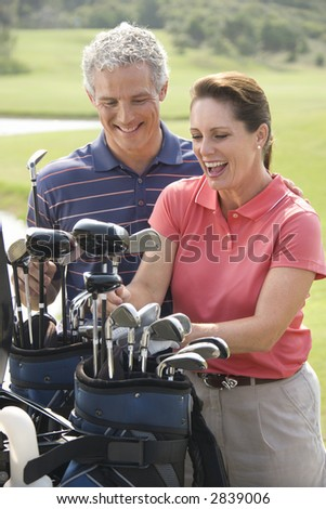 Caucasion mid-adult man and woman smiling and picking out golf club. - stock photo