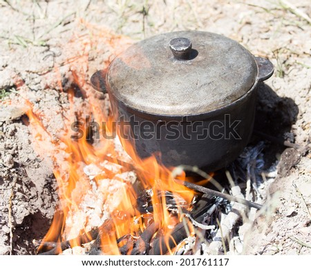 cauldron on the fire on the nature - stock photo