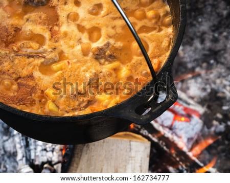 Cauldron with bograch (goulash) on fire - stock photo
