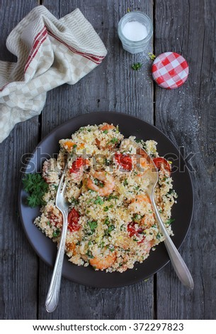 Cauliflower couscous with cherry tomatoes, shrimps, lemon, parsley in a plate on a wooden table, selective focus - stock photo