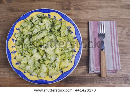 Cauliflower dish with a fork and a napkin on a rustic wooden table. Typical dish of Mediterranean diet. - stock photo
