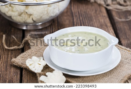 Cauliflower Soup in a small bowl (close-up shot) on wooden background - stock photo