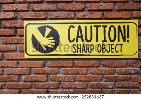 Caution Sign On Brick Wall,Beware Sharp Object - stock photo