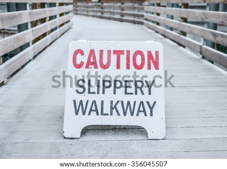 caution slippery walkway warning sign on the walk way cover with the ice in the park. - stock photo