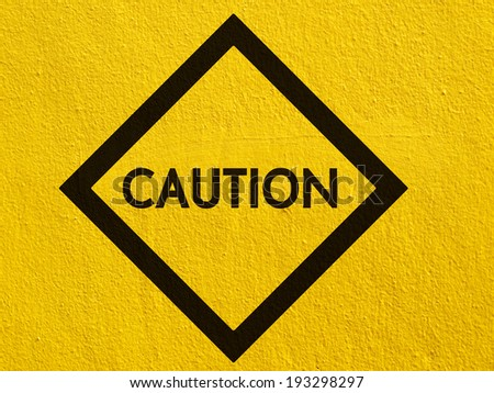 caution traffic sign painted on a stucco wall outside - stock photo