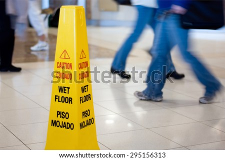 Caution Wet Floor sign with people walking in the background - stock photo
