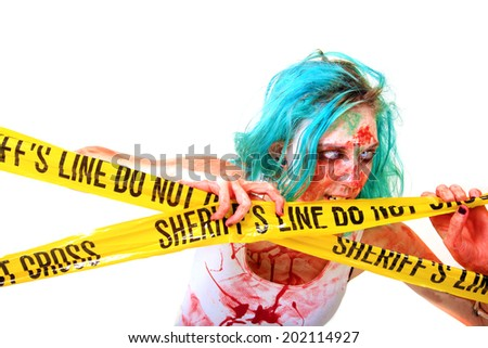 "CAUTION ZOMBIES!!!! A blue haired member of the Un-Dead aka ZOMBIE Chews on and looks through Real ""Sheriffs Line Do Not Cross"" Crime Scene Yellow plastic tape. Isolated on white with room for text - stock photo"