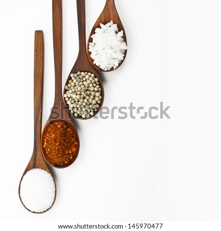 Cayenne, pepper, salt and sugar. Arranged in a wooden spoon. - stock photo