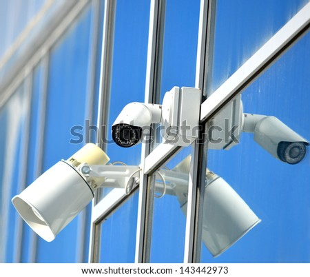 CCTV camera and loudspeaker on a glass facade outdoors - stock photo
