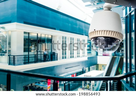CCTV Camera of Surveillance operating in blue building - stock photo