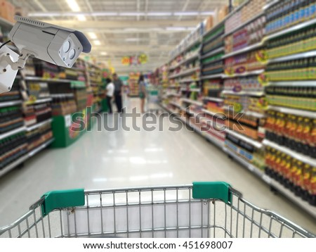 CCTV camera on blurred of store with trolley in department store  - stock photo