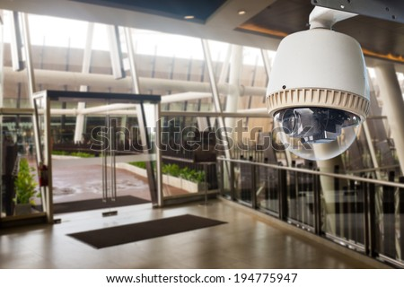 CCTV Camera operating in front of glass door - stock photo