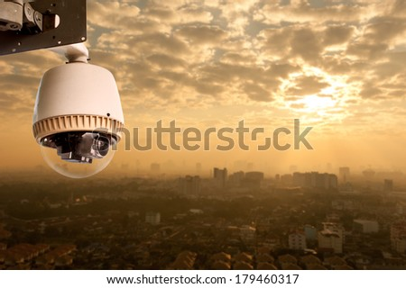 CCTV Camera Operating with city in background - stock photo
