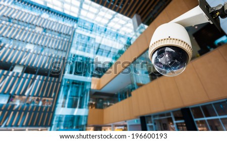 CCTV Camera or surveillance operating on window building - stock photo
