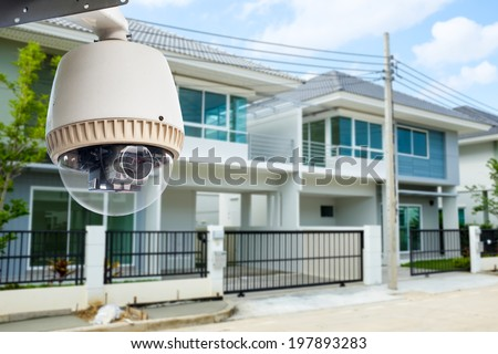 CCTV Camera or surveillance operating with house village in background - stock photo