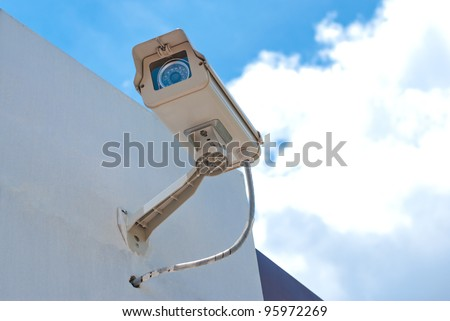 CCTV security camera at home and blue sky - stock photo