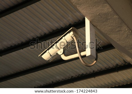 CCTV security camera in a train station - stock photo