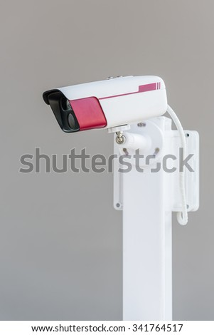 CCTV security camera on grey background - stock photo