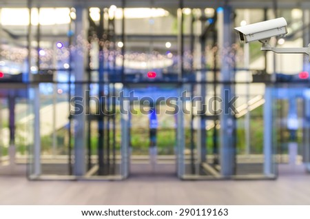 CCTV security camera on monitor the Abstract blurred photo of glass elevation with bokeh background - stock photo