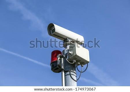 CCTV security camera under blue sky - stock photo