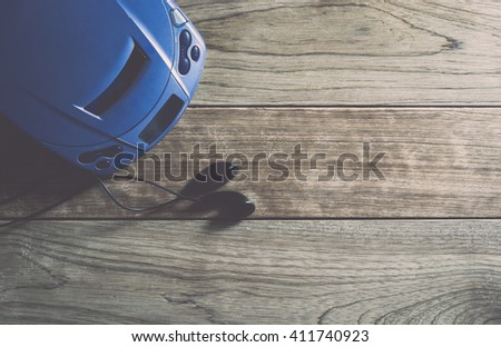 CD player and earphones on wooden plank under warm light - stock photo