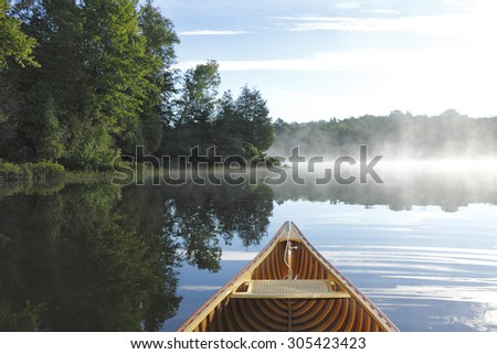Cedar Canoe Bow on a Misty Lake - Haliburton, Ontario, Canada - stock photo