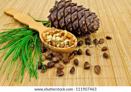 Cedar nuts, cedar bump, cedar nut kernels in a wooden spoon and a green sprig of cedar on a bamboo mat - stock photo