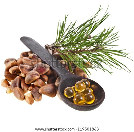 cedar pine nuts and essential oil ball  in spoon  isolated on white background close up - stock photo
