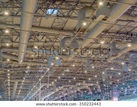Ceiling lighting and ventilation pipes - stock photo