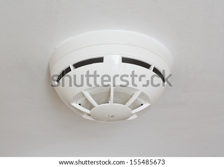ceiling mounted white fire detector used to activate warning systems in residential buildings - stock photo