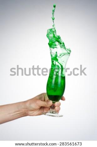celebrate the holiday background - hand with alcohol cocktail making toast - wonderful splash - stock photo