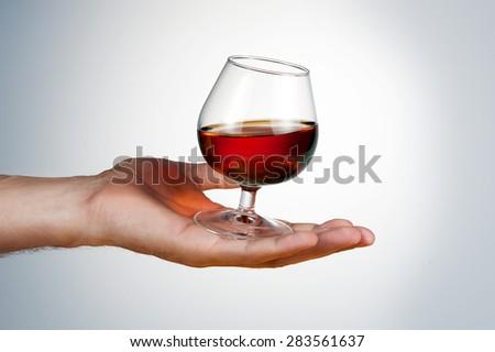 celebrate the holiday background - hand with cognac making toast - wonderful splash - stock photo