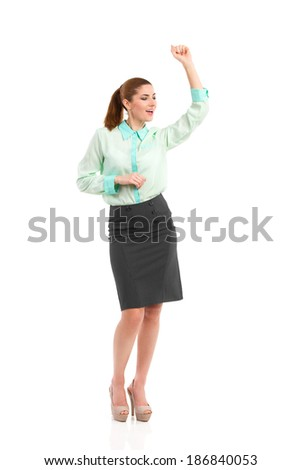 Celebrating businesswoman. Smiling attractive woman dancing and singing with arm raised. Full length studio shot isolated on white. - stock photo