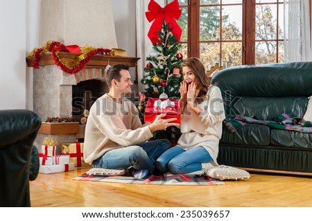 Celebrating Christmas together. Beautiful young couple sitting on the floor in christmas decorated living room exchanging presents and smiling  - stock photo