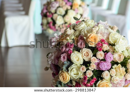 Celebrating hall decorated with wedding bunches of fresh beautiful flowers of roses and peony white pink violet purple yellow lilac and orange colours round shape indoor and chairs, horizontal picture - stock photo