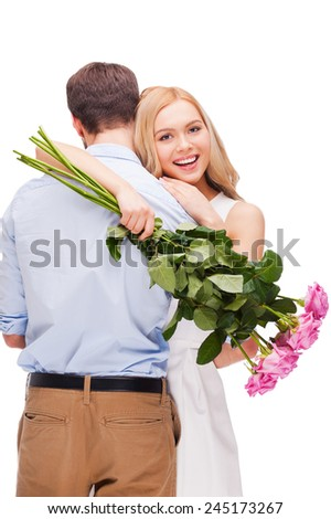 Celebrating love. Beautiful young loving couple hugging while woman holding bouquet of pink roses and smiling and both standing isolated on white background   - stock photo