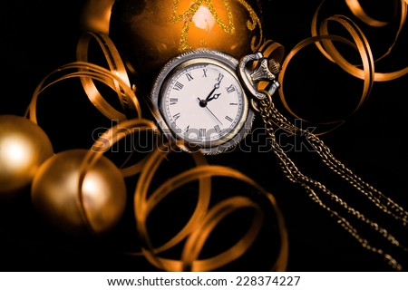 Celebrating New Year Eve concept with vintage watch, baubles and decoration ribbon on black (toned image) - stock photo
