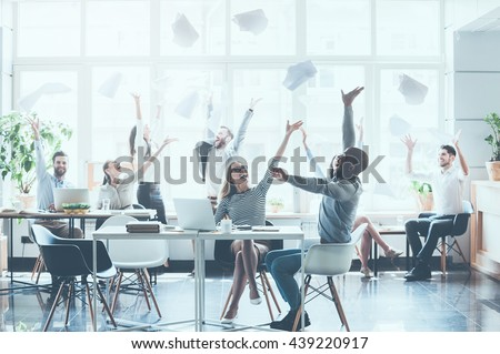 Celebrating success. Group of young business people throwing documents and looking happy while sitting at their working places in office  - stock photo
