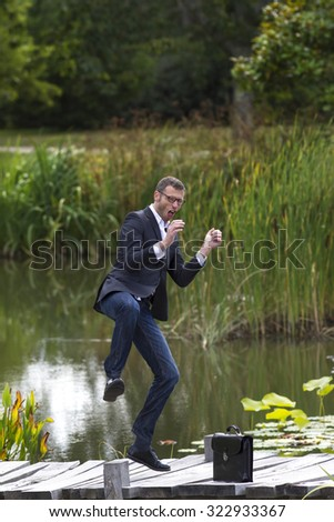 celebrating success outdoors concept - dynamic modern businessman with eyeglasses dancing for fun corporate achievement on bridge near water,natural summer daylight - stock photo