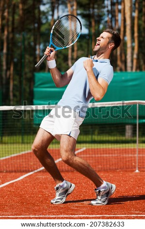Celebrating success. Side view of happy young man in polo shirt holding tennis racket and gesturing while standing on tennis court  - stock photo