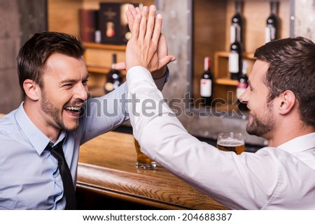 Celebrating success together. Two cheerful young men in shirt and tie talking to each other and gesturing while drinking beer at the bar counter  - stock photo
