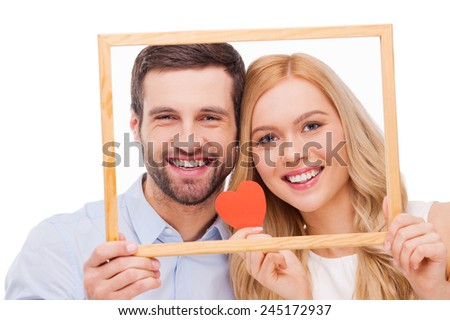 Celebrating their love. Beautiful young loving couple bonding to each other and holding heart shape paper while looking through a frame and standing isolated on white background  - stock photo